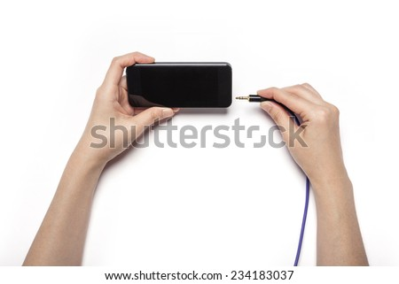 A female(woman) hand hold a black mobile phone with earphone cable(plug, socket) isolated white, top view at the studio.