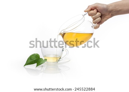 A female(woman) hand hold a glass tea pot to tea cup isolated white at the studio