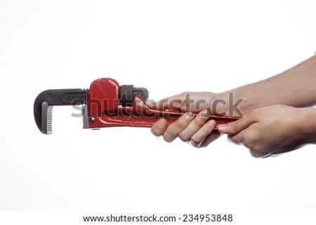 A female(woman) hand hold a red monkey wrench(spanner) isolated white at the studio. - stock photo