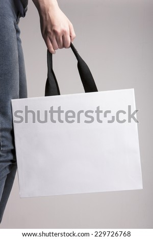 A female(woman) hand hold a white shopping bag(paper bag) and black strings at the studio. - stock photo