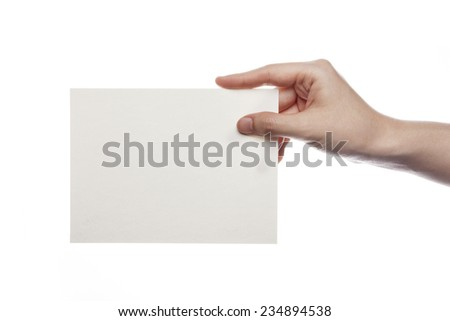 A female(woman) hand hold(pick up) a empty(blank) paper(post card) isolated white at the studio.