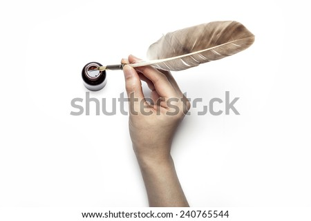 A female(woman) hand hold(write) a feather quill pen into the ink. - stock photo