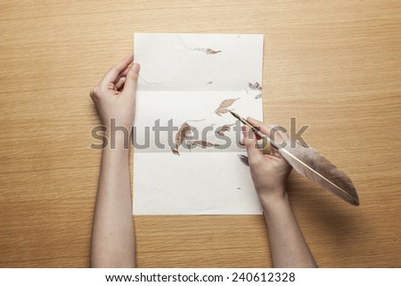 A female(woman) hand hold(write) a feather quill pen on the letter paper and wood desk(table) top view at the studio. - stock photo