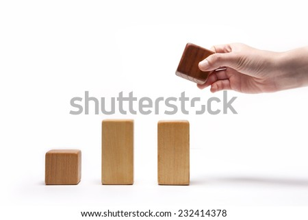 A female(woman) hand pick up(hold) a wood block among Color wood cube blocks like bar graph symbolizing sales growth isolated white at the studio. - stock photo