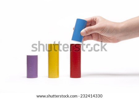 A female(woman) hand pick up(hold) a wood block among Color wood cylinder blocks(yellow, red, blue, purple) like bar graph symbolizing sales growth isolated white at the studio. - stock photo
