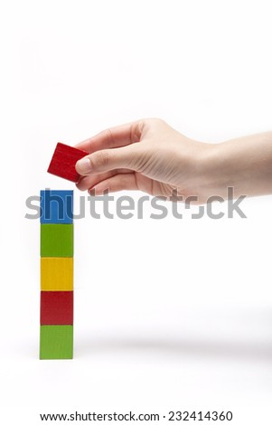 A female(woman) hand pick up(hold) a wood block among many color(red, yellow, blue, green) wood blocks like bar graph symbolizing sales growth isolated white at the studio. - stock photo