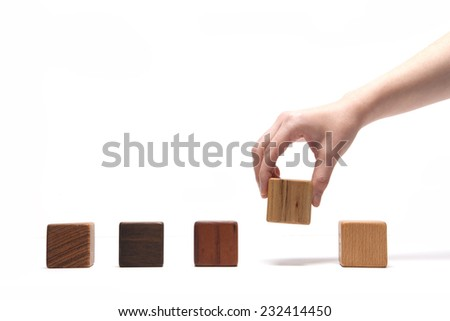 A female(woman) hand pick up(hold) a wood block among many wood blocks(oak, walnut, teak, cherry) isolated white at the studio. - stock photo