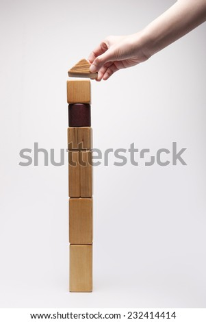 A female(woman) hand pick up(hold, make) the high tower(house, building) with wood blocks symbolizing real estimate isolated white at the studio. - stock photo