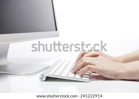 A female(woman) hand touch(push) the white keyboard with computer isolated white at the studio.
