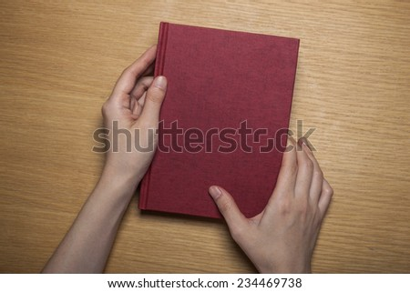 A female(woman) hands hold a blank(empty) red book(note, diary) cover on the wood desk(table), top view at the studio. - stock photo