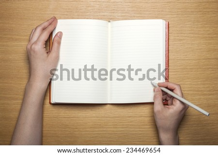 A female(woman) hands hold a blank(empty) red book(note, diary) with pencil on the wood desk(table), top view at the studio. - stock photo