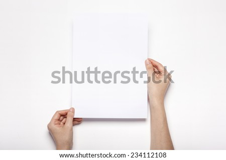 A female(woman) hands hold a empty(blank) white paper(a4) isolated white, top view at the studio. - stock photo