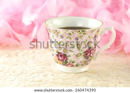 A feminine floral rose teacup filled with hot fresh tea with a pink background for copy-space