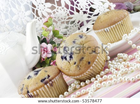 A feminine tea party  with fresh baked blueberry muffins - stock photo