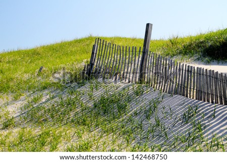 A fence crosses sand dunes at Island Beach State Park, New Jersey - stock photo
