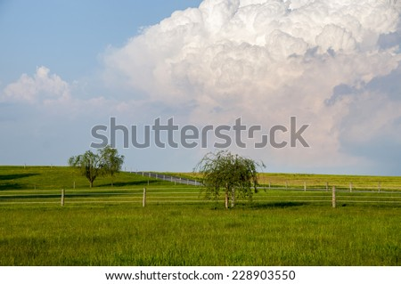 A fenced meadow on a bright sunny day with a threatening thunderhead cloud over head. - stock photo