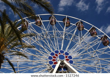 A ferris wheel framed by palm trees at an outdoor shopping center in Irvine, California. - stock photo