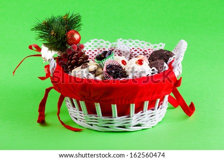a festive christmas basket filled with cookies and candy over a green background - stock photo