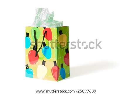A festive gift bag with tissue paper coming out.