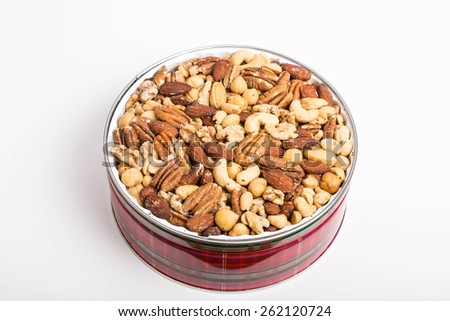 A festive red tin of deluxe mixed nuts on a white counter - stock photo