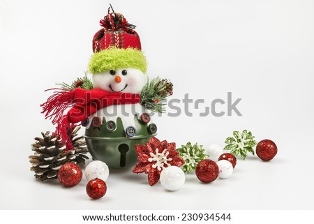 A festive snowman ornament on a white background with colorful Christmas holiday baubles and pine cones.  Room for copy space.