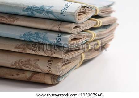 A few bills of brazilian currency (real) on white background