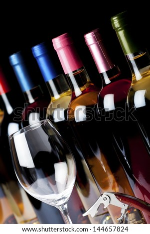 A few bottles of wine, corkscrew and a wine glass on a black background - stock photo