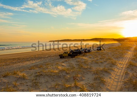 A few cars on a deserted beach at sunset, Queensland, Austraila - stock photo