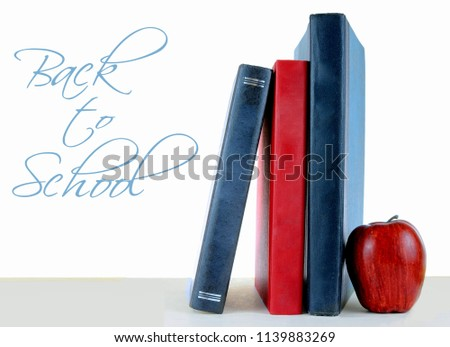 A few dusty books standing up on a light table with a white background. An apple is beside the books. Back to school message added