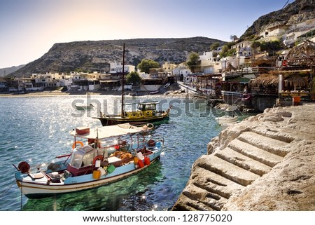 A few fishing boats moored in Matala (on Crete island in Greece) at sunrise. Bars, restaurants and hotels in the background. - stock photo