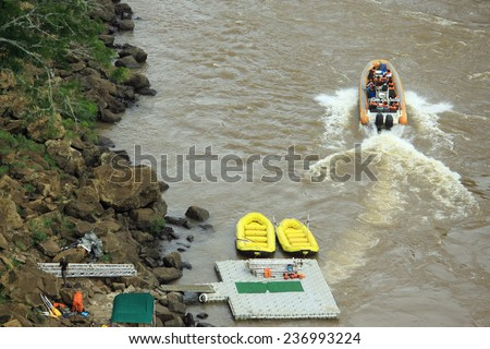 a few inflatable boats near Iguacu waterrfalls on the border of Argentina and Brazil - stock photo