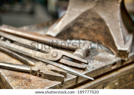 A few metal crafting tools laying next to an anvil in a metal fabrication shop. - stock photo