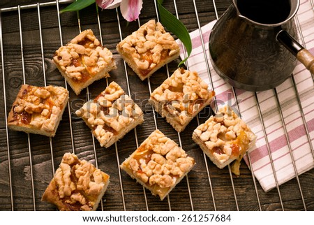 A few pieces of pie with apples and apricot jam on a baking and coffee pot. Image tinting - stock photo