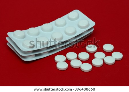 A few scattered white pills and packs of tablets in foil on a red background
