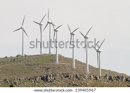 A few wind turbines on the top of an arid hill