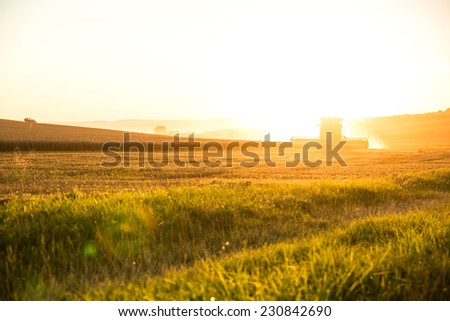 A field getting harvested by a agricultural machine. - stock photo