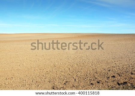 A field of plowed ground on a background of blue sky. - stock photo