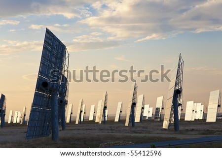 A field of solar mirror panels harnessing the sun's rays to provide alternative green energy at sunrise or sunset - stock photo