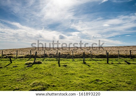 A field separated by 2 fences in the mountains. - stock photo
