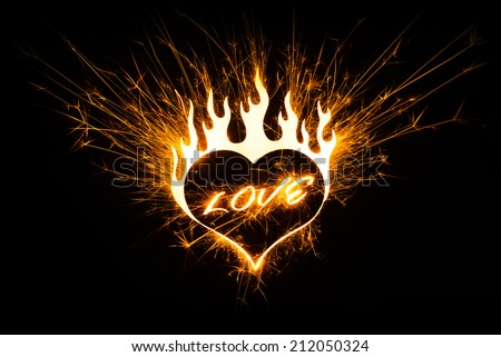 A fiery hot love symbol on black background  with copy space. - stock photo