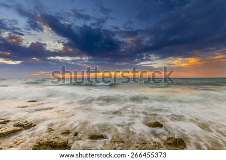 a fiery sunset and the waves lapping on the rocky shore