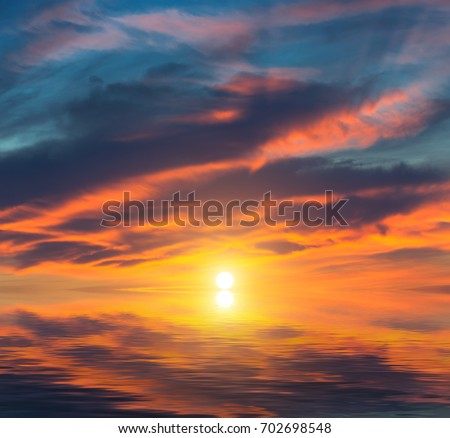A fiery sunset on the sea and blood-red clouds. Natural sunset composition
