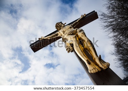 a figure of Christ crucified on an old cemetery in Regensburg - stock photo