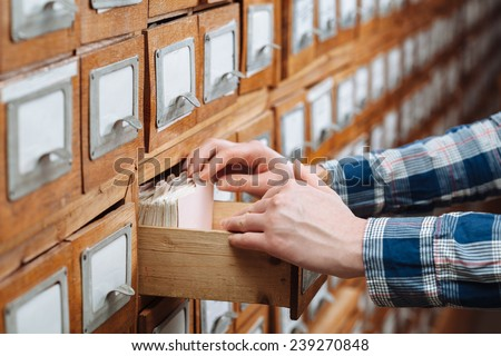 A file cabinet drawer full of files opened by woman hand - stock photo