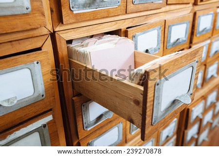 A file cabinet drawer full of files/ wooden shelf - stock photo
