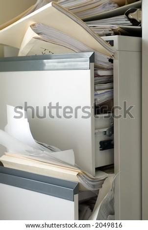 A file cabinet filled beyond capacity ... total disorder - stock photo
