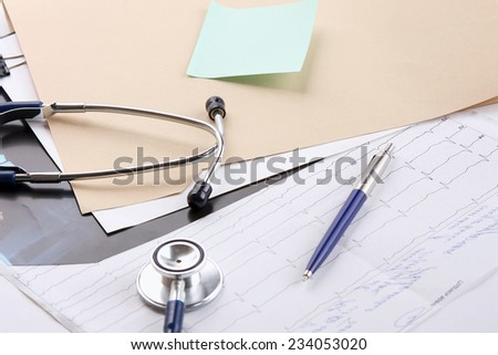 a file folder, a stethoscope and a pen on ekg - stock photo