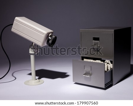 A filing cabinet and a security camera in a spotlight.