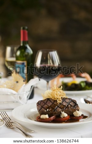 A fillet mignon steak dinner with a bottle and glass of red wine in a fine restaurant setting. - stock photo
