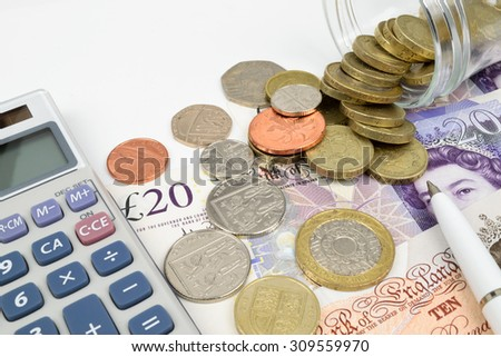 A finance still life with a jar of Sterling coins on Sterling notes, calculator and pen. - stock photo